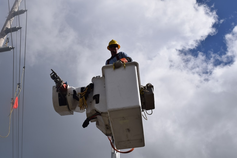 "The Army Corps of Engineers Task Force Power Restoration continues their mission through the holidays. Corps Quality Assurance Specialist Amy Tillery observes as a contracted crew from Mas-Tec erect transmission lines Christmas morning. Residences and businesses in the area have been without power for over 100 days. Patrick Foreman, a lineman operating an auger pole truck at the construction site, said he was overwhelmed with the people's kindness. ""My whole crew just wants to finish our work here as safely and quickly as possible, so these fine people can return to a normal life."""