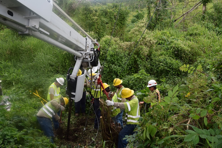 The U.S. Army Corps of Engineers Task Force Power Restoration continues their mission through the holidays. Corps Quality Assurance Specialist Amy Tillery observes as a contracted crew from Mas-Tec persist with a stubborn pole anchor and guy, while working to straighten a recently placed power pole Christmas morning. The previous pole along with most others in the area had either been broken or toppled by Hurricane Irma and Maria. Residences and businesses in the area have been without power for over 100 days.