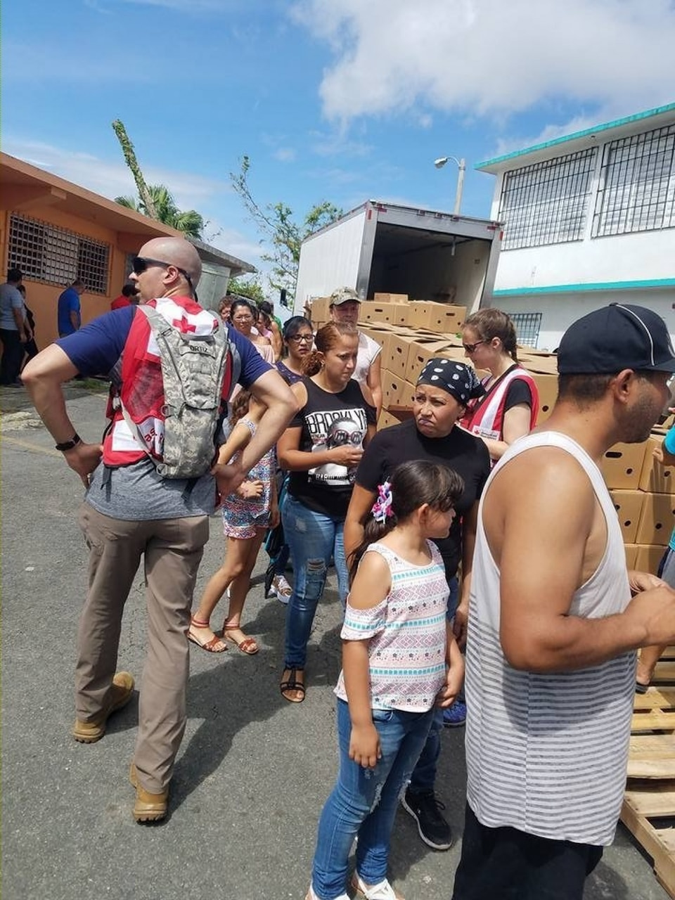 Army Sgt. 1st Class Rafael Ortiz, left, a cybersecurity noncommissioned officer with the 781st Military Intelligence Battalion and a Red Cross team leader, works with a member of his team to provide assistance items to local residents in Ortiz's hometown during a humanitarian mission in Naranjito, Puerto Rico, Oct. 15, 2017. Courtesy photo