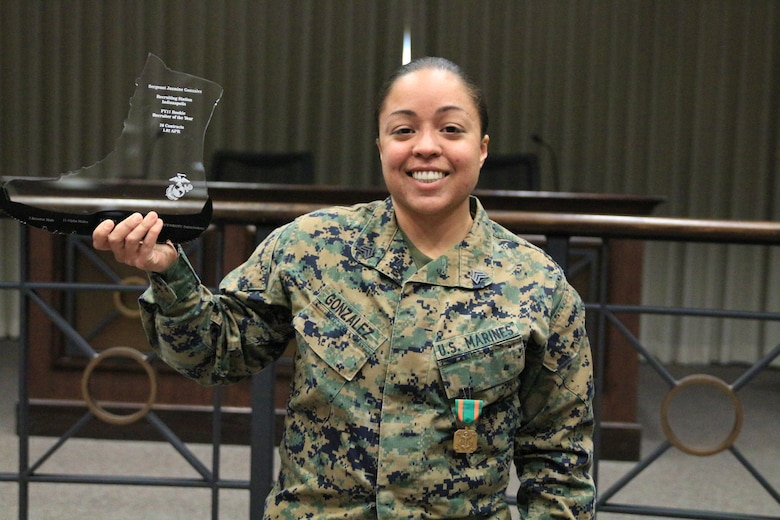 Sgt Jasmine Gonzalez holds her Rookie Recruiter of the Year trophy while wearing her Navy and Marine Corps Achievement Medal. Sgt Gonzalez was the fiscal year 2017 Rookie Recruiter of the Year for Recruiting Station Indianapolis.