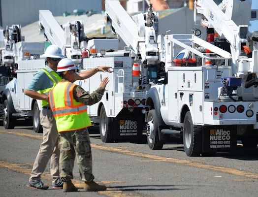 electrical workers talk near vehicles