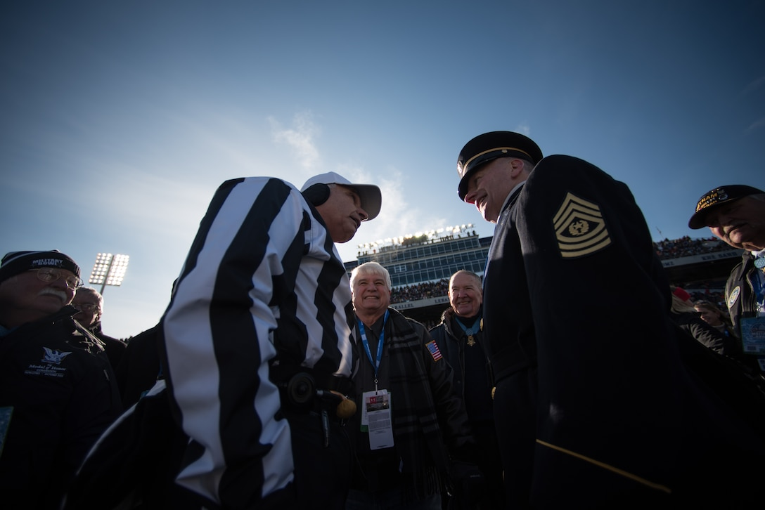 Army Command Sgt. Maj. John W. Troxell stands across from a football game referee.