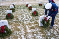 Image of Coast Guard Sector Anchorage crewmember placing a wreath on a veteran's grave.