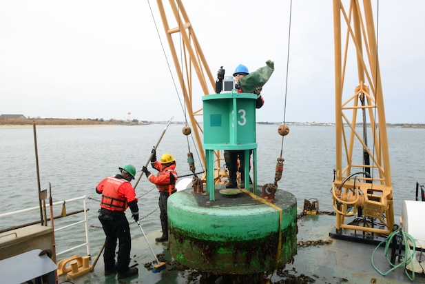 Image of Coast Guard crew working aids to navigation buoys.