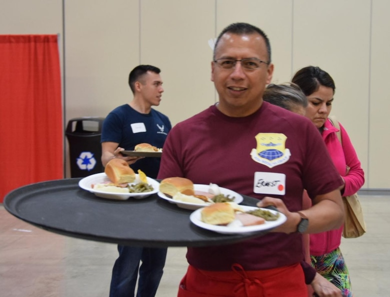 Senior Airman Leslie Ybarra, 433 Aerospace Medicine,  Squadron, medical technician carries a tray of plates to guests at the H-E-B's 25th Annual Feast of Sharing on Dec. 23, 2017, at the Henry B. Gonzalez Convention Center in San Antonio, Texas. Ybarra was among 40 Alamo Wing members, friends and family, who helped the afternoon shift of volunteers serve up dinners at the Henry B. Gonzalez Convention Center in San Antonio, Texas. (U.S. Air Force photo by Tech. Sgt. Carlos J. Treviño)