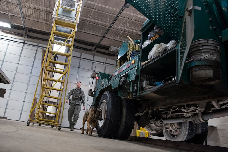 Senior Airman Karissa Fitzpatrick, 21st Security Forces Squadron military working dog handler, and her dog Dano conduct a vehicle check at the East Gate Commercial Vehicle Checkpoint at Peterson Air Force Base, Colorado, on Dec. 22, 2017. Military working dog handlers are responsible for checking vehicles coming onto base for prohibited items. (U.S. Air Force photo by Steve Kotecki)