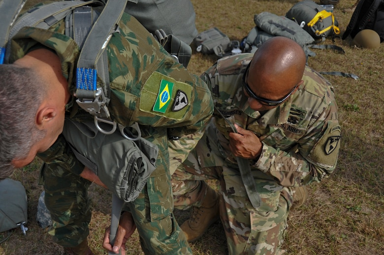 "A Jumpmaster with 7th Special Forces Group (Airborne) performs jumpmaster inspection on a Brazilian paratrooper during ""Operation Toy Drop"" yielding over 300 toys for the affected families of Hurricane Maria in Puerto Rico."