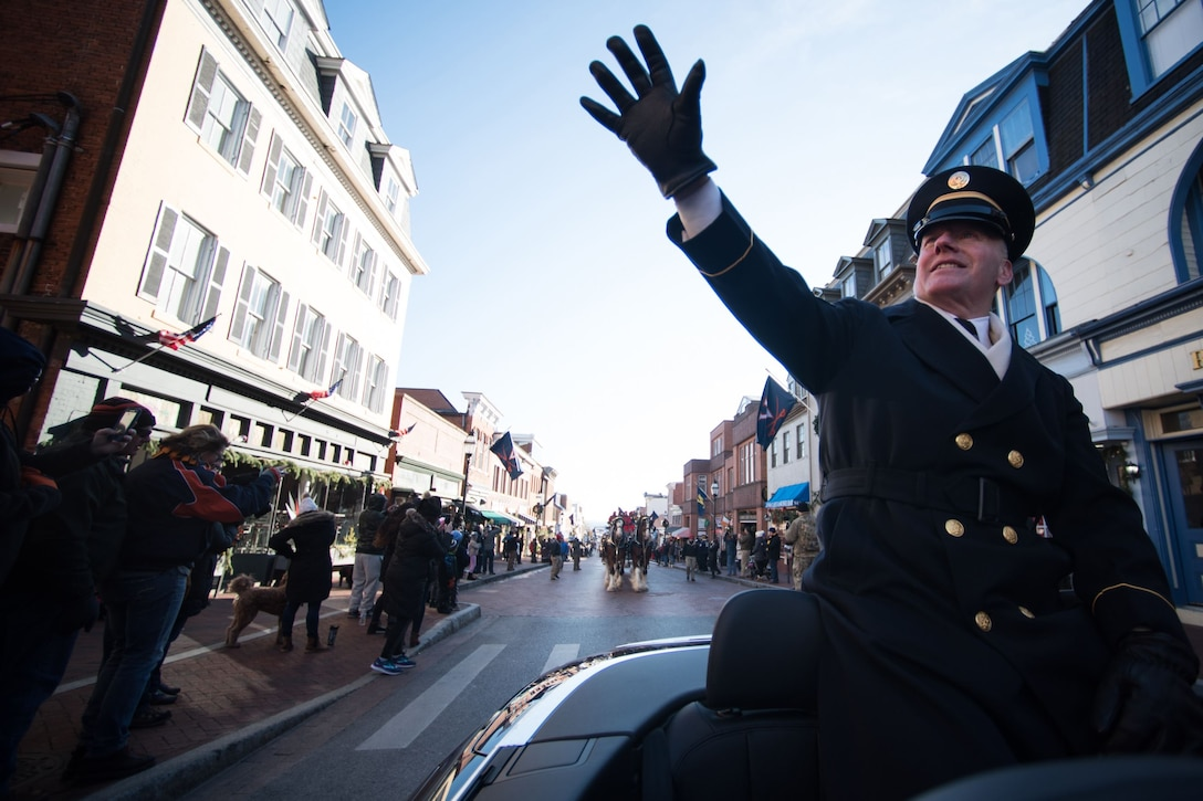 Army Command Sgt. Maj. John W. Troxell waves to a crowd from the backseat of a car.