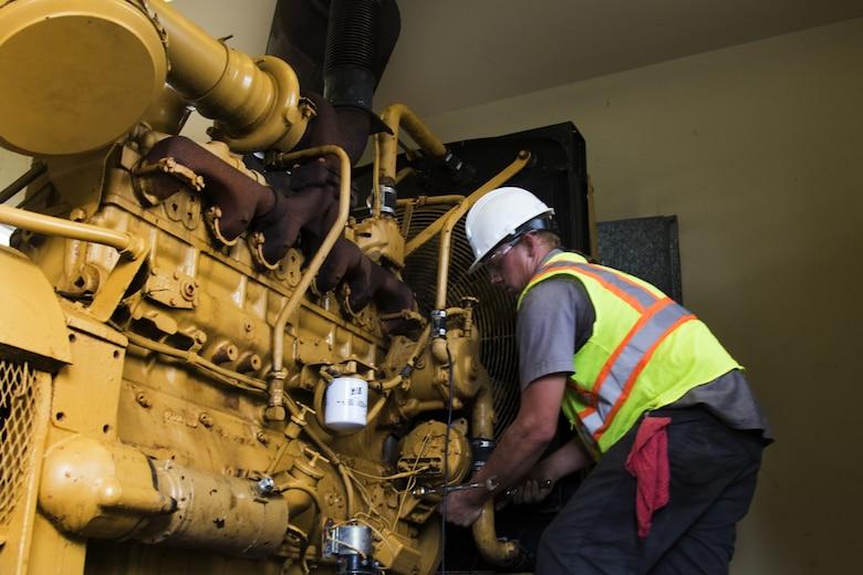 man fixes old generator