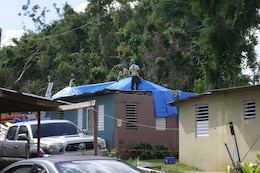 workers install blue roof