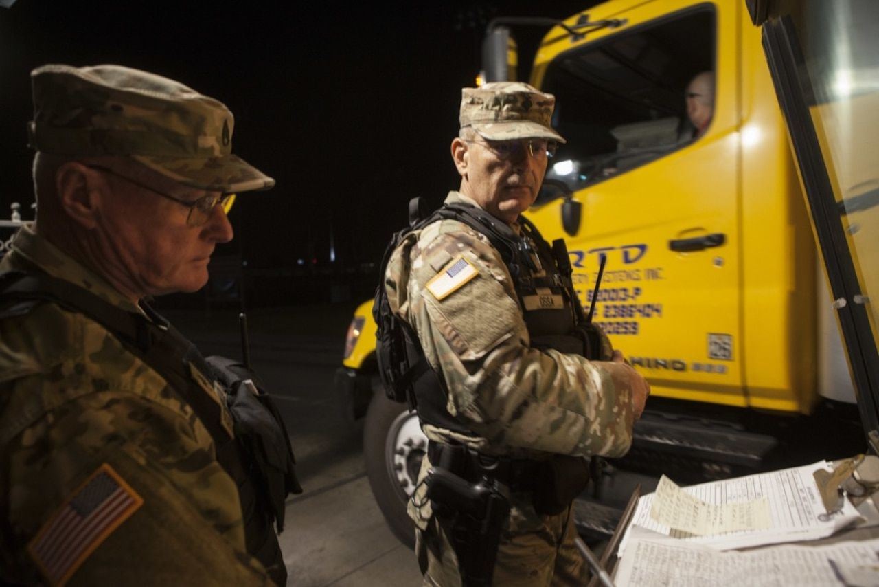 California State Military Reserve Staff Sgt. James Fitzgerald, left, and California State Military Reserve Spc. Juan Ossa, right, both with the Installation Support Command, finish logging delivering supplies.