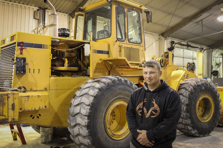 man stands in front of heavy equipment