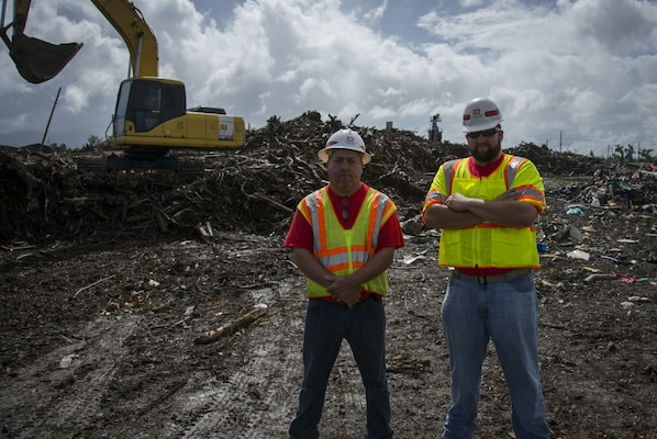 two men stand in debris yard in Puerto rico