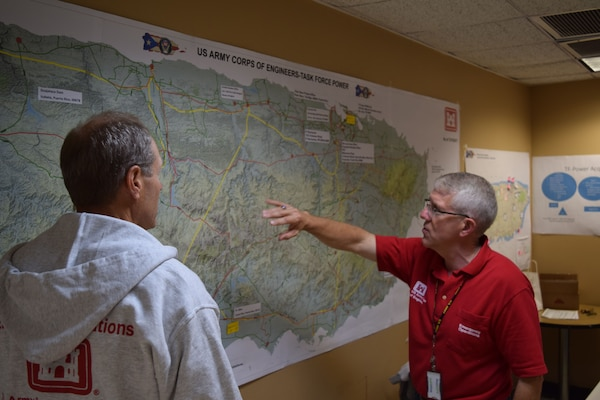 Task Force Power Restoration Program Manager, Philip R. Tilly (right), shows Jay Field, TF Power public affairs, the path the storm took as it made landfall onto Puerto Rico, Sept. 20.