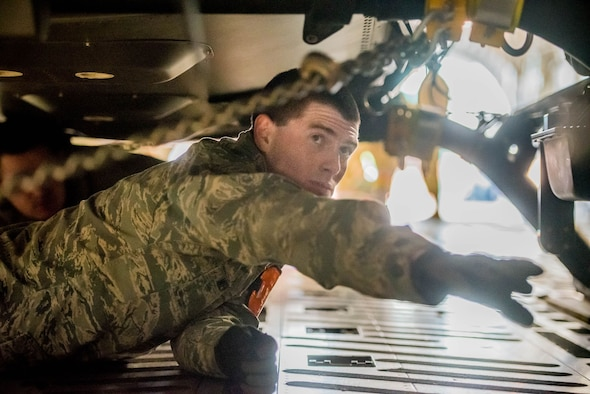 Staff Sgt. Kaleb Wentworth, an aerial port specialist with the Kentucky Air National Guard's 123rd Logistics Readiness Squadron, chains a Kentucky Army National Guard helicopter to the floor of an aircraft at the Kentucky Air National Guard Base in Louisville, Ky., on January 27, 2017.  Wentworth was selected from among more than 1700 aerial porters as the top transportation journeyman in the Air National Guard for 2016.