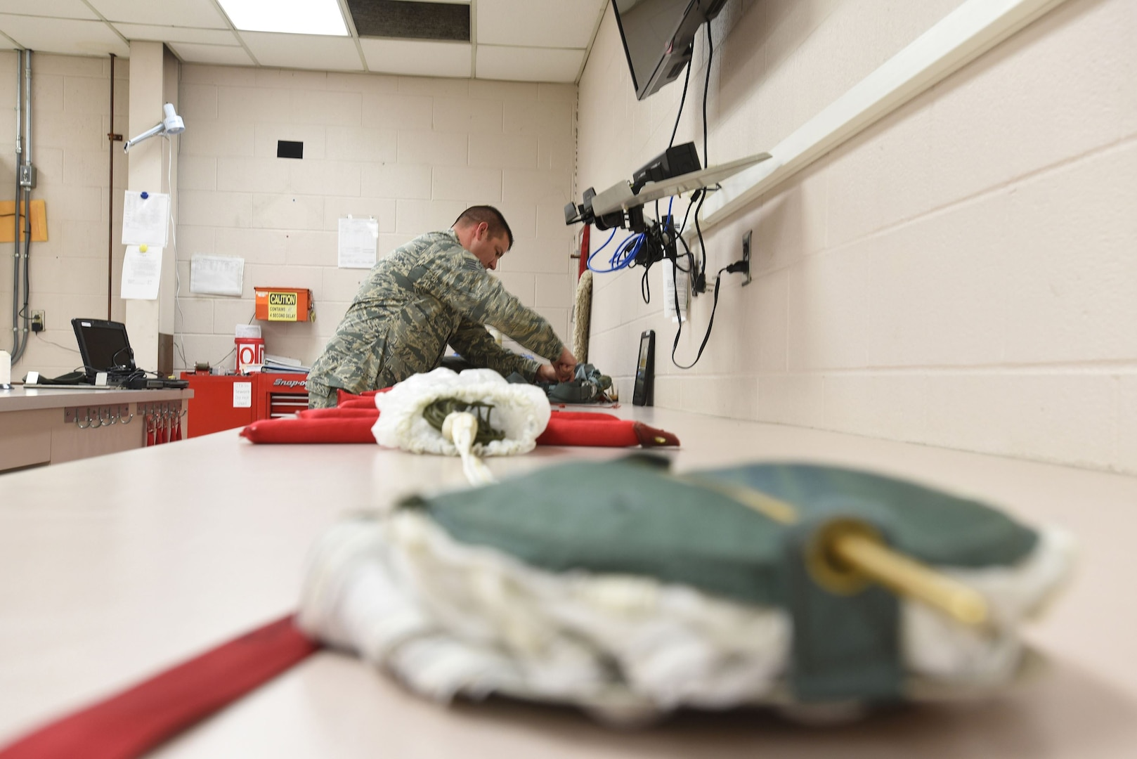 Tech. Sgt. Christopher Brawner, an aircrew flight equipment journeyman with the Kentucky Air Guard's 123rd Operations Support Squadron in Louisville, Ky., repacks a parachute after performing routine maintenance June 9, 2017. The parachute is just one of the many life-saving devices that are put aboard aircraft by members of the aircrew flight equipment shop after careful inspection