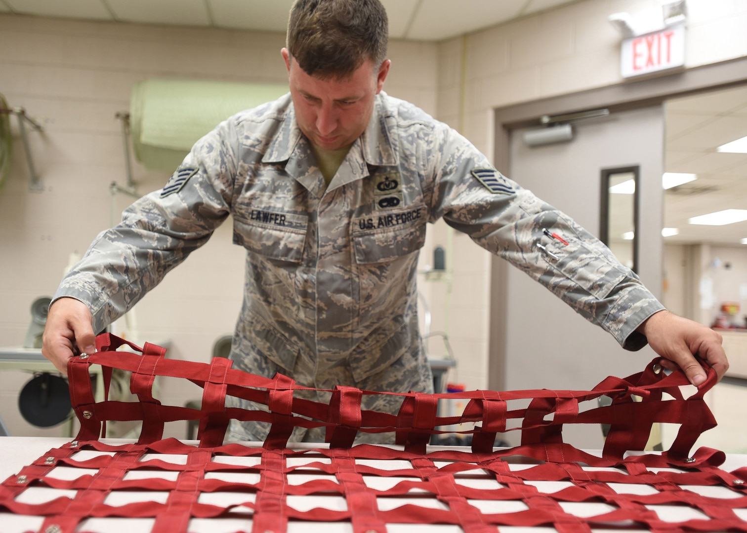 Tech. Sgt. Lawrence Lawfer, an aircrew flight equipment journeyman with the Kentucky Air Guard's 123rd Operations Support Squadron in Louisville, Ky., inspects and identifies tears and other deficiencies on an aircraft seat harness June 9, 2017. The repair of life-saving equipment is the responsibility of the aircrew flight equipment shop here.