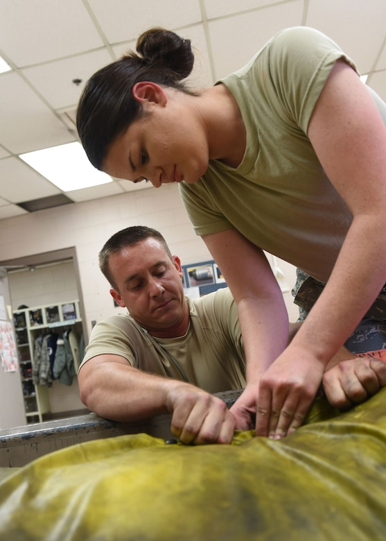 Master Sgt. David Clark (left), an aircrew flight equipment journeyman, and Airman 1st Class Cheyenne Underwood, an aircrew flight equipment apprentice, both with the Kentucky Air Guard's 123rd Operations Support Squadron in Louisville, Ky., pack a rubber raft after a routine inspection of its integrity June 9, 2017. Each piece of life-saving equipment that goes on an aircraft has a specific maintenance schedule, which is the responsibility of the aircrew flight equipment shop.