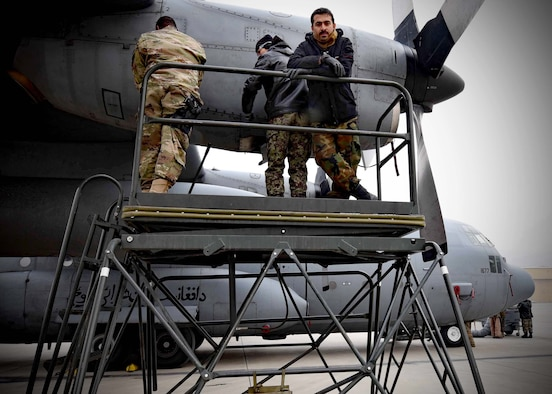 Tech. Sgt. Toron Bordain, 440th Air Expeditionary Advisory Squadron, C-130 maintenance advisor, works with his Afghan Air Force counterparts to remove an engine panel for training at Kabul Air Wing, Afghanistan, Jan. 18, 2017. Bordain, an Air Force Reservist out of Dobbins Air Reserve Base, Ga., is part Train, Advise, Assist Command-Air (TAAC-Air), working to develop a professional, capable and sustainable Afghan Air Force. (U.S. Air Force photo by Tech. Sgt. Veronica Pierce)