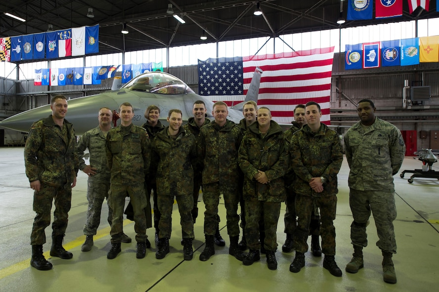 German air force members and U.S. Air Force Airmen pose in front of an F-16 Fighting Falcon in Hangar 1 at Spangdahlem Air Base, Germany, Jan. 31, 2017. The German af visited as part of their Advanced Air Mission Control Course, and the group will also being visited Buechel AB and Polygone Control Center, Bann, Germany, on the tour. (U.S. Air Force photo by Senior Airman Dawn M. Weber)