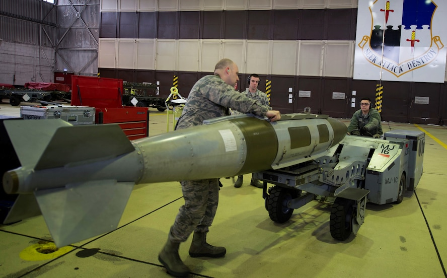U.S. Air Force Airman 1st Class Brandon Shoulta, 52nd Aircraft Maintenance Squadron aircraft armament specialist, positions an MJ-IC jammer in Hangar 1 during a tour for members of the German air force at Spangdahlem Air Base, Germany, Jan. 31, 2017. The German af was given a tour of visiting various facilities such as the fitness center, the tower and Hangar 1 as a way to bolster U.S. and German partnerships. (U.S. Air Force photo by Senior Airman Dawn M. Weber)