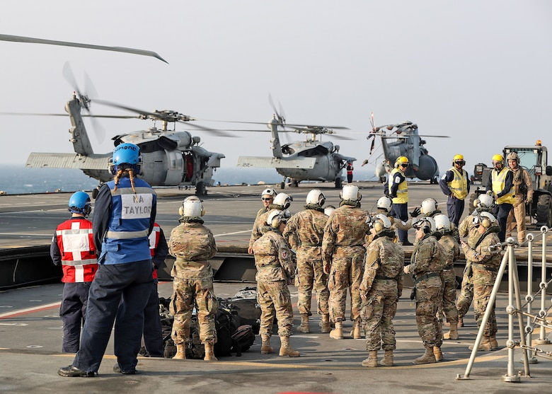 The 379th Expeditionary Medical Operations Squadron mobile field surgical and critical care teams embark on the HMS Ocean via a U.S. Navy SH-60 Sea Hawk helicpoter, Jan. 23, 2017. The MFST-ECCT medical personnel participated in exercise Azraq Serpent, where they joined coalition forces to simulate setting up a role two surgical and critical care facility on a maritime platform. (Courtesy photo, Royal Navy)