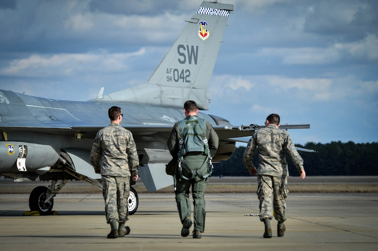 (From left) Staff Sgt. Dominic Dizes, F-16 Viper Demonstration Team dedicated crew chief, Capt. John Waters, F-16 Viper Demonstration Team pilot, and Senior Airman Adam Armstrong, F-16 Viper Demonstration Team dedicated crew chief, walk out to their aircraft for a 9th Air Force certification flight at Shaw Air Force Base, S.C., Jan. 20, 2017. The F-16CM Fighting Falcon is a fourth generation fighter aircraft that can withstand nine times the force of gravity, or nine G's, which exceeds the capability of all other fourth generation fighter aircraft. (U.S. Air Force photo by Senior Airman Michael Cossaboom)