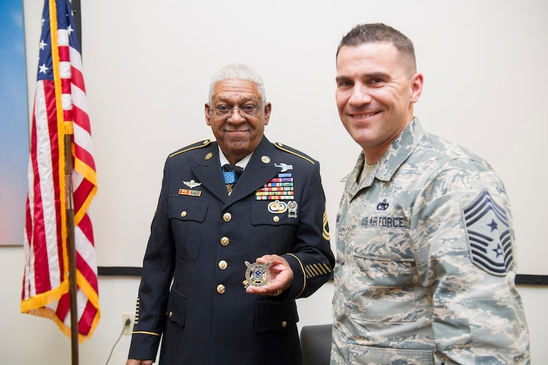 Chief Master Sgt. Jason Lamoureux, 45th Space Wing command chief, coins Medal of Honor recipient retired U.S. Army Sgt. 1st Class Melvin Morris at Patrick AFB, Fla., Jan. 31, 2017. Lamoureux thanked him for his bravery, courage and inspirational message to our service members on the power of the human spirit. (U.S. Air Force photo by Phil Sunkel)