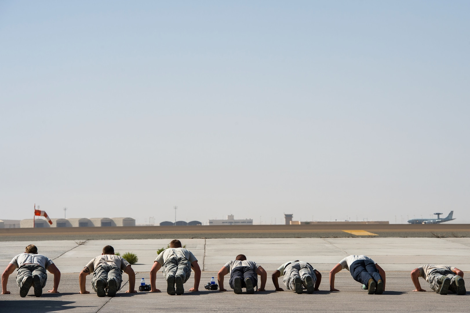 380th Expeditionary Aircraft Maintenance Squadron Airmen complete pushups while an E-3 Sentry departs and completes a sortie in support of Combined Joint Task Force-Operation Inherent Resolve at an undisclosed location in Southwest Asia, Feb. 2, 2017. The E-3 Sentry maintainers complete as many push-ups as possible while the aircraft takes off. Since November 2016, no E-3 Sentry has missed a scheduled sortie due to maintenance issues. (U.S. Air Force photo by Senior Airman Tyler Woodward)