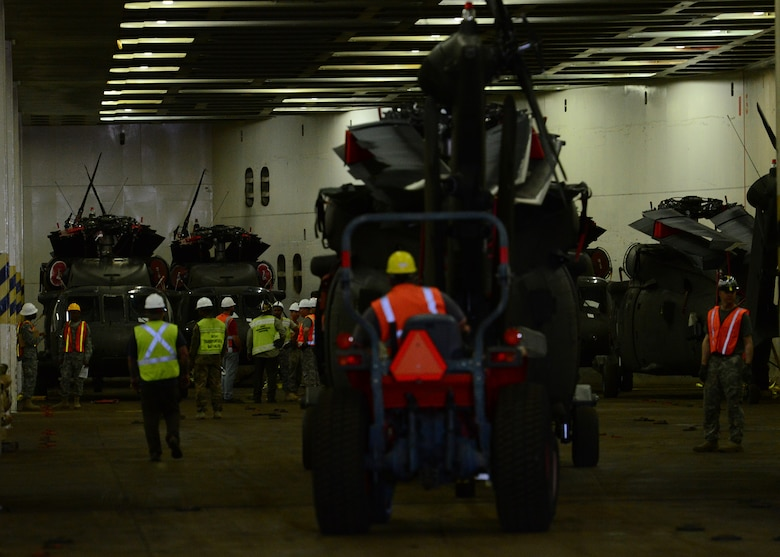 Department of Defense-contracted longshoremen on-load helicopters form the 10th Combat Aviation Brigade (CAB). More than 900 pieces of equipment were loaded onto the transport ship ARC Endurance, January 25, 2017, at Joint Base Charleston, S.C. – Weapons Station. Members from the 10th Combat Aviation Brigade and the 841st Transportation Battalion staged, processed and configured the equipment in support of Operation Atlantic Resolve 2.0.