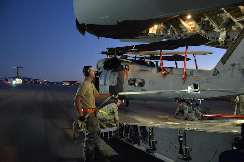 To ensure the flying safety of Air Force choppers used to save lives in combat, maintenance crews from the 920th Rescue Wing swap out an HH-60G Pave Hawk helicopter for reconditioning January 25, 2017. A team of 10 maintainers is necessary to skillfully muscle the metal warrior into the cargo bay however, more often join the unique event for hands-on training and to secure the warrior on a smooth journey over an ocean and a continent to trade places with the combat-weary aircraft. (U.S. Air Force photo/Maj. Cathleen Snow)