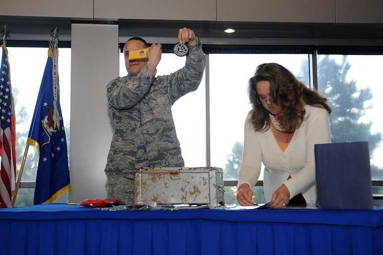 Staff Sgt. Jared Wiedmer and Kristin Heikkila, both 50th Contracting Squadron, present items before placing them in a time capsule during a ceremony at Schriever Air Force Base, Colorado, Monday, Jan. 30, 2017.  The time capsule was buried in the northwest corner of Building 210 with instructions to open June 1, 2049, the 100th anniversary of the 50th Space Wing at Schriever. (U.S. Air Force Photo/Dennis Rogers)