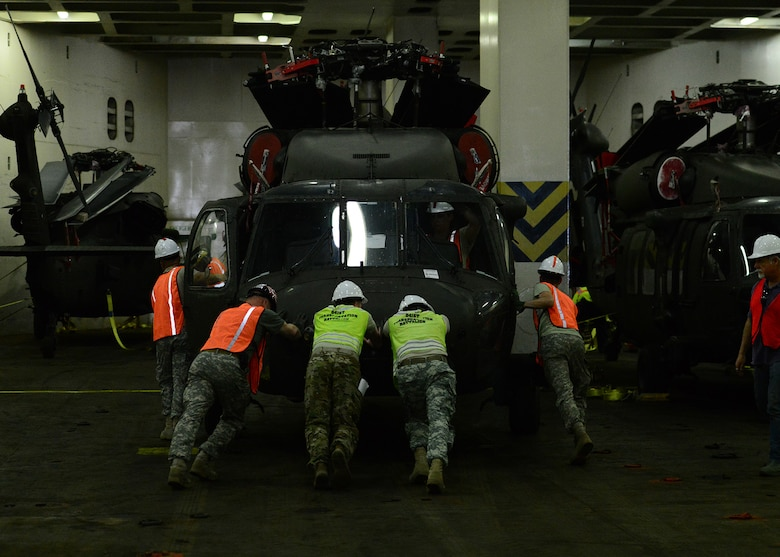 Soldiers from the 841st Transportation Battalion (TB) and the 10th Combat Aviation Brigade  (CAB) move helicopters into position to be strapped down and secured for transport aboard the transport ship ARC Endurance, for shipment to overseas. The 841st TB's mission is to conduct surface deployment and redeployment distribution and water terminal operations in support of the warfighter.