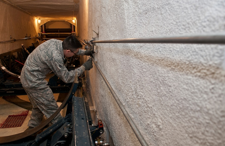 Airman 1st Class Antonio Torres, 91st Missile Maintenance Squadron missile handling team technician, inspects transporter erector sling rods at Minot Air Force Base, N.D., Jan. 19, 2017. When the MHT is at a launch facility, they are directly involved in the installation or removal of the nuclear capable Minuteman III missile's booster stages. (U.S. Air Force photo/Airman 1st Class Jonathan McElderry)