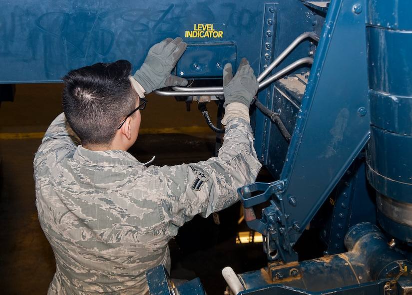 Airman 1st Class Antonio Torres, 91st Missile Maintenance Squadron missile handling team technician, re-installs a level indicator cover at Minot Air Force Base, N.D., Jan. 19, 2017. The level indicator allows the MHT to ensure the transporter erector is properly level while in use. (U.S. Air Force photo/Airman 1st Class Jonathan McElderry)