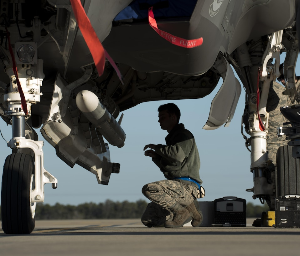 U.S. Air Force Airman 1st Class Dylan Snead, 33rd Aircraft Maintenance Squadron weapons load crew member, secures a live AIM-120 advanced medium-range air-to-air missiles (AMRAAM)  onto a weapons jammer before loading it into an F-35A January 31, 2017, at Eglin Air Force Base, Florida. The 33rd Fighter Wing loaded and shot the first air-to-air missiles from an F-35A during a weapons system evaluation that took place at Tyndall Air Force Base later the same day. Carrying air-to-air missiles makes the F-35 a more versatile option for combatant commanders by securing the aircrafts survivability, in turn increasing likeliness of mission success.  (U.S. Air Force photo by Staff Sgt. Peter Thompson)