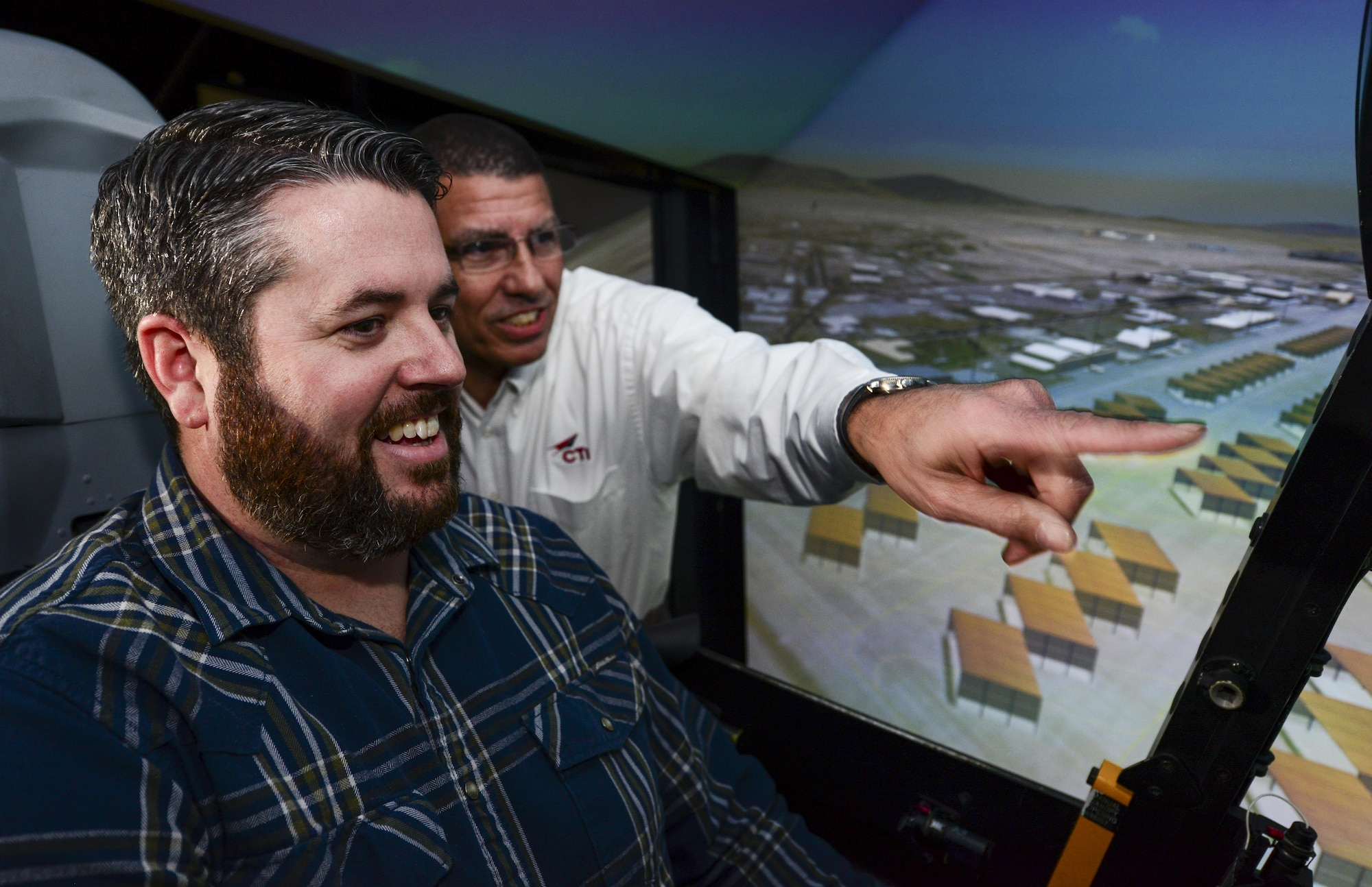Retired U.S. Air Force Lt. Col. Gregg Montijo points ahead while Marcus Foiles pilots an A-10 flight simulator at Davis-Monthan Air Force Base, Ariz., Jan. 27, 2017. Foiles was 10 years old in 1989 when he was granted a trip to D-M via the Make-A-Wish Foundation after being diagnosed with leukemia. Foiles made the trip back to D-M to reconnect with Montijo, the pilot who hosted the tour 28 years ago. (U.S. Air Force photo by Airman 1st Class Nathan H. Barbour)