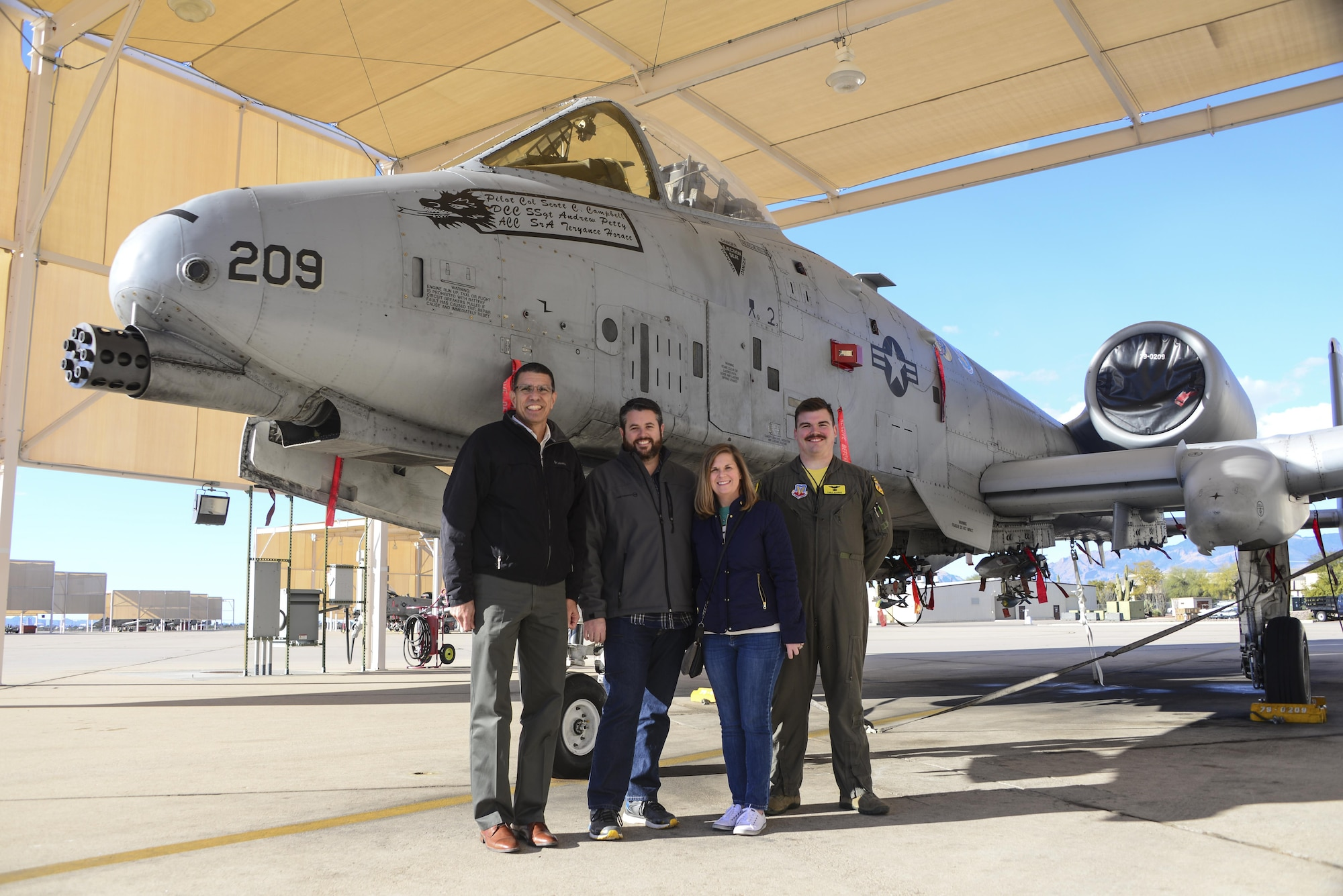 Retired U.S. Air Force Lt. Col. Gregg Montijo, Marcus Foiles, his wife Melanie, and 1st Lt. Christopher McBride, 355th Training Squadron A-10 pilot, pose for a photo on the flight line at Davis-Monthan Air Force Base, Ariz., Jan. 27, 2017. Foiles was 10 years old in 1989 when he was granted a trip to D-M via the Make-A-Wish Foundation after being diagnosed with leukemia. Foiles made the trip back to D-M to reconnect with Montijo, the pilot who hosted the tour 28 years ago. (U.S. Air Force photo by Airman 1st Class Nathan H. Barbour)
