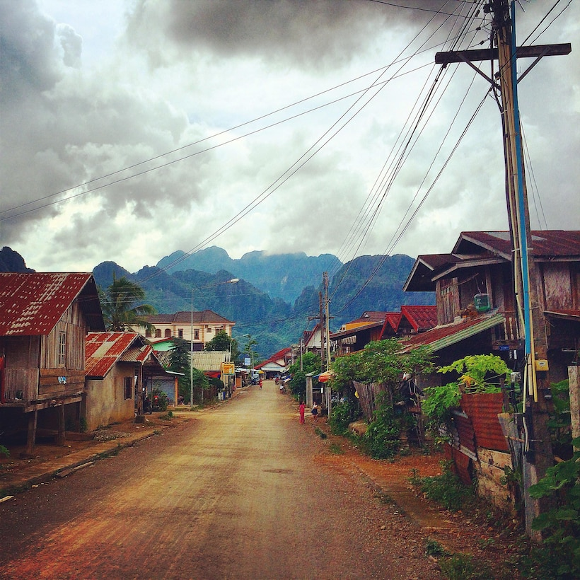 This photo sets the relatively well-developed town of Vang Vieng, with its roads and power lines, into the contextual reality of Lao PDR's mountainous terrain.  The Lao population benefits from higher road access and rural electrification rates than other countries at the same per capita income level.