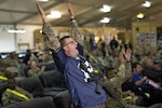 Capt. Joe Beale, a systems automation officer assigned to the 57th Expeditionary Signal Battalion and deployed to Kandahar Airfield, Afghanistan, cheers as the Seattle Seahawks score a touchdown during Super Bowl XLVIII, Feb. 2, 2014. DLA Troop Support's Subsistence supply chain helped ensure service members enjoy traditional fare for this year's big game.