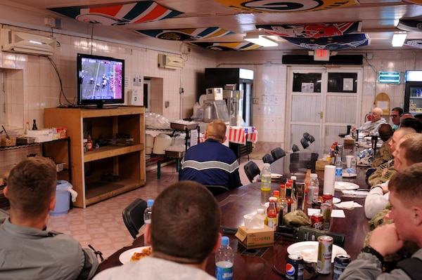 Members of Zabul Provincial Reconstruction Team watch Super Bowl XLVII at Forward Operating Base Smart, Afghanistan, Feb. 4, 2013. DLA Troop Support's Subsistence supply chain helped ensure service members enjoy traditional fare for this year's big game.