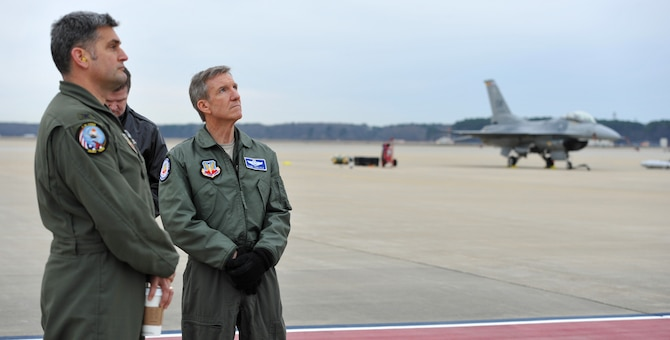 """Gen. Hawk Carlisle (right), commander of Air Combat Command, watches alongside Col. Douglas Thies, 20th Operations Group commander and Maj. Gen. Thomas Deale, ACC A3, as Capt. John """"Rain"""" Waters flies his F-16 Fighting Falcon in a demonstration in hopes of qualifying as a pilot for the 2017-18 F-16 demonstration team Feb. 1, 2017 at Langley Air Force Base, Va. Demonstration pilots, who perform at air shows worldwide, serve two-year tours on their respective teams, and must be certified at multiple levels. Carlisle, as COMACC, was Waters' final level of certification, and named him as a demo pilot immediatley after the flight. (U.S. Air Force photo by Emerald Ralston)"""