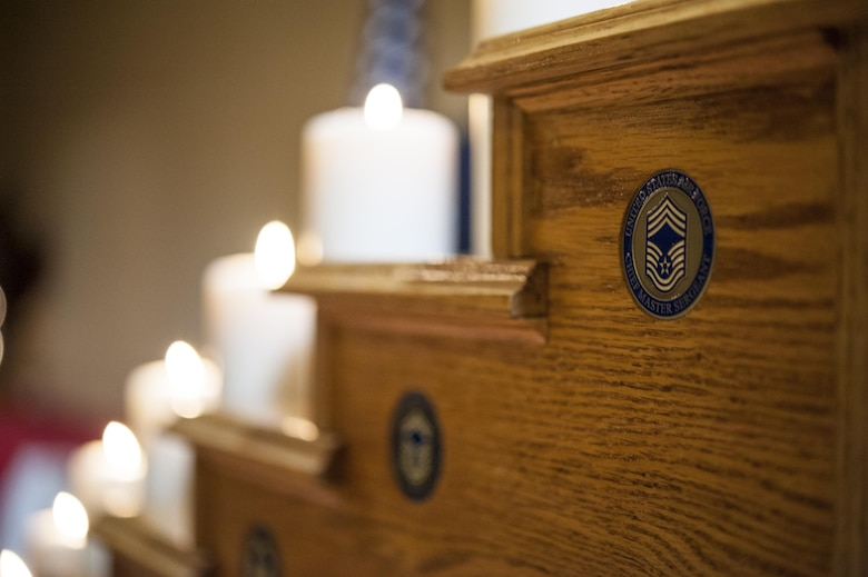 A chief coin rests in a ceremonial candle display at the Chief Induction Ceremony, Jan. 28, 2017, at Moody Air Force Base, Ga. The candles signify the climb up the rank structure. The induction ceremony is a time-honored tradition that recognizes Airmen as they make the transition from senior master sergeant to chief master sergeant. (U.S. Air Force photo by Andrea Jenkins/Released)