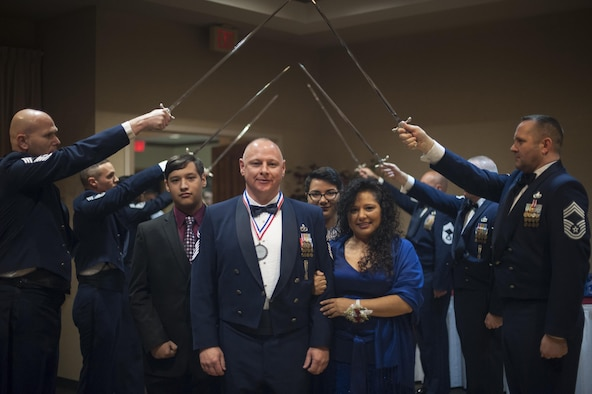 Senior Master Sgt. Michael Reed, 23d Equipment Maintenance Squadron production section superintendent, and his family walk through the ceremonial saber detail, signifying his transition to the rank of chief master sergeant, at the Chief Induction Ceremony, Jan. 28, 2017, at Moody Air Force Base, Ga. The induction ceremony is a time-honored tradition that recognizes Airmen as they make the transition from senior master sergeant to chief master sergeant. (U.S. Air Force photo by Andrea Jenkins/Released)