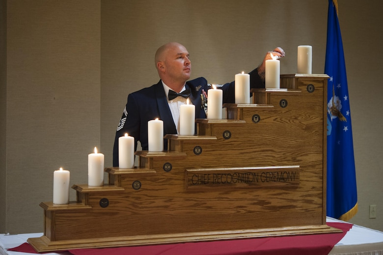 Senior Master Sgt. Kevin Jenkins, 23d Maintence Group weapons standardization superintendent, lights a ceremonial candle at the Chief Induction Ceremony, Jan. 28, 2017, at Moody Air Force Base, Ga. The candles signify the climb up the rank structure. The induction ceremony is a time-honored tradition that recognizes Airmen as they make the transition from senior master sergeant to chief master sergeant. (U.S. Air Force photo by Andrea Jenkins/Released)