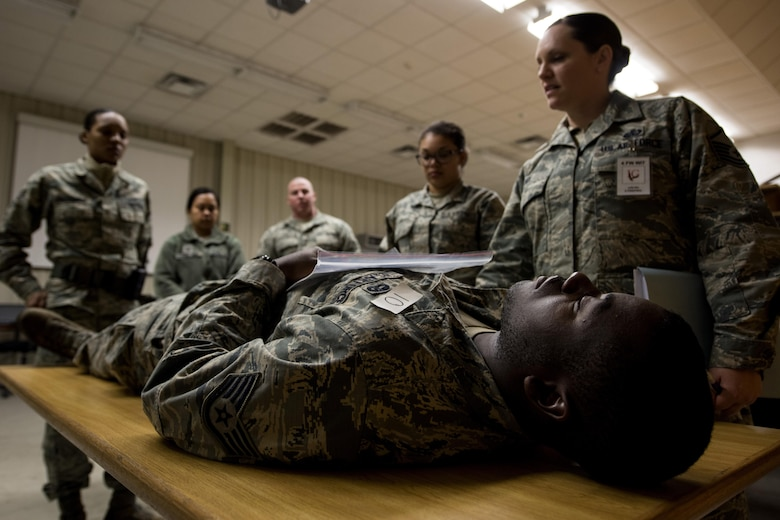 Staff Sgt. Damyan Jackson, 4th Logistic Readiness Squadron vehicle operator, acts as a casualty during exercise Coronet Warrior 17-01, Jan. 31, 2017, at Seymour Johnson Air Force Base, North Carolina. Master Sgt. Julie Nix, 4th Force Support Squadron wing inspection team member, evaluated the mortuary affairs procedures of participating 4th FSS Airmen. (U.S. Air Force photo by Airman Shawna L. Keyes)