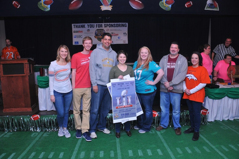 Nick Schuster, in the gray Minnesota Football sweatshirt of Veterans United Home Loans, the title sponsor for Super Saturday is seen here with his staff and the Super Saturday Bingo winner Maj. Kelly Borukhovich,20th Intelligence Squadron, to his right. The Offutt Air Force Base's Super Saturday event was at the Patriot Club on Jan. 21. The event included live and silent auctions of sports mermorbelia and Bingo to determine who wins the grand prize of an all expenses paid trip for two to Super Bowl LI. (U.S. Air Force photo by D.P. Heard)