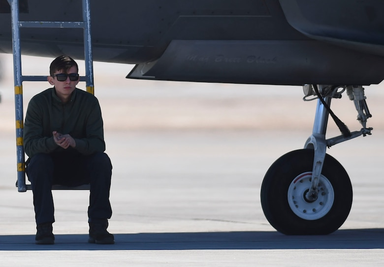 U.S. Air Force Airman 1st Class Brian Dowling, 27th Aircraft Maintenance Unit crew chief, takes a break while waiting for an F-22 Raptor pilot to arrive to his jet during Red Flag 17-1 at Nellis Air Force Base, Nev., Jan. 26, 2017. Crew chiefs conduct preflight checks before pilots arrive to ensure that all aircraft maintenance safety measures are in standards. (U.S. Air Force photo by Staff Sgt. Natasha Stannard)