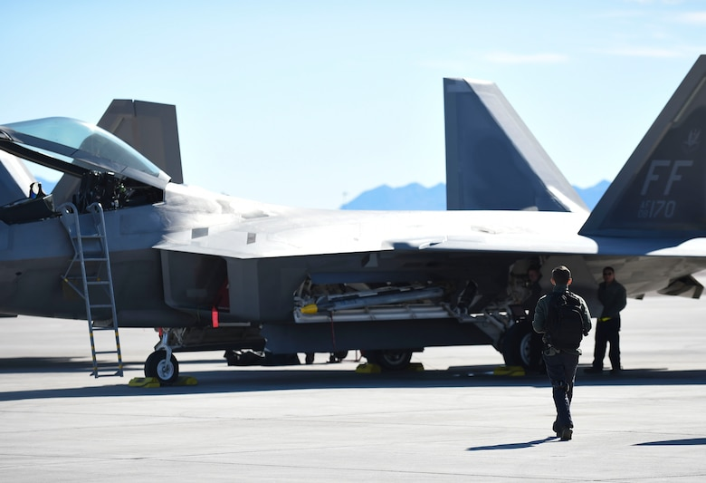 U.S. Air Force Airman 1st Class Brian Dowling, 27th Aircraft Maintenance Unit crew chief, walks out to an F-22 Raptor to conduct preflight inspections during Red Flag 17-1 at Nellis Air Force Base, Nev., Jan. 26, 2017. This is Dowling's first time participating in the U.S. Air Force's premiere large-force air, cyber and space exercise. (U.S. Air Force photo by Staff Sgt. Natasha Stannard)
