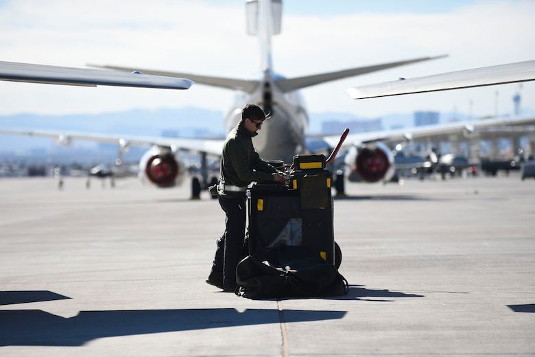 U.S. Air Force Airman 1st Class Brian Dowling, 27th Aircraft Maintenance Unit crew chief, checks his equipment before conducting preflight inspections on an F-22 Raptor during Red Flag 17-1 at Nellis Air Force Base, Nev., Jan. 26, 2017. Red Flag 17-1 includes not only Raptor aircrews and support, but fellow fifth generation F-35A Lightning II crews. (U.S. Air Force photo by Staff Sgt. Natasha Stannard)